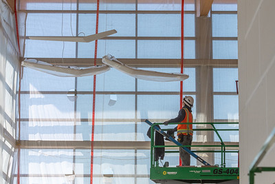 An electrician with Mill Plain Electric prepares to install wing-shaped light fixtures. (Josh Kulla/DJC)