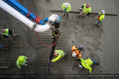 Last year, cement masons poured concrete on a Portland multifamily project. Construction workers have filed multiple complaints in recent weeks about the lack of social distancing on job sites. (Josh Kulla/DJC file)