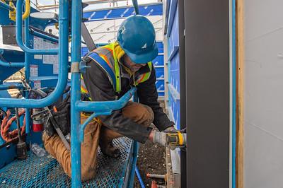 Daniel Green, a journeyman sheet metal technician with Local 16 and an employee of Arctic Sheet Metal, installs architectural metal panels on the building's exterior. (Josh Kulla/DJC)