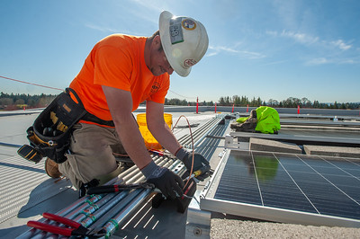 Chris Paren, a journeyman electrician with IBEW Local 48 and a solar foreman with Mill Plain Electric, wires solar panels on the buildings roof. (Josh Kulla/DJC)