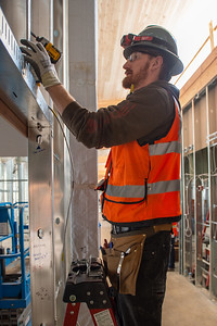 Gauge Thompson, an apprentice electrician with IES Commercial and Industrial, installs a wall receptacle. (Josh Kulla/DJC)