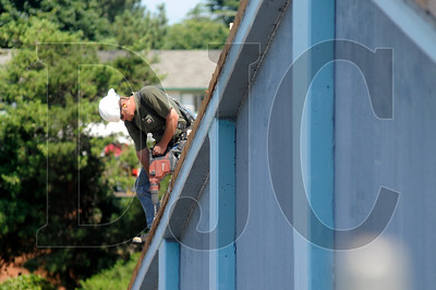 Tom White, a journeyman carpenter with Cor Construction and a member of Carpenters Local 156, drills holes for anchor bolts for the seismic upgrade of a roof at Floyd Light Middle School in Portland on Wednesday.