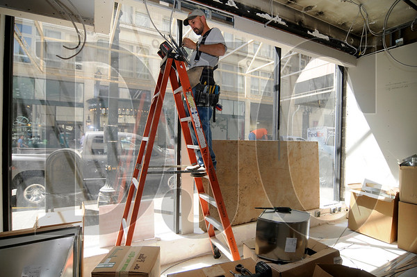 Wes Schreiber, an electrician with Whiskey Hill Electric, wires lines for a motorized window shade at the site of a future Chase Bank branch in downtown Portland on Thursday.  Chase Bank is looking to open 30 branches in the Portland Metro area over the course of the next three years.