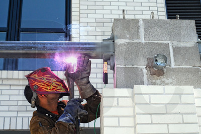 PJ Pulido, a welder with Lorentz Bruun Construction, works on a patio canopy at the Parker Apartments in the Pearl District.