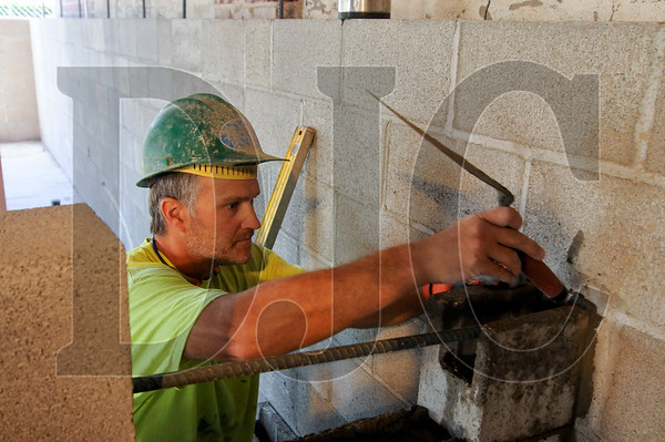 Justin Hunt, a mason with Creative Design Masonry, works on a partition wall at the Breathe Building in Southeast Portland.