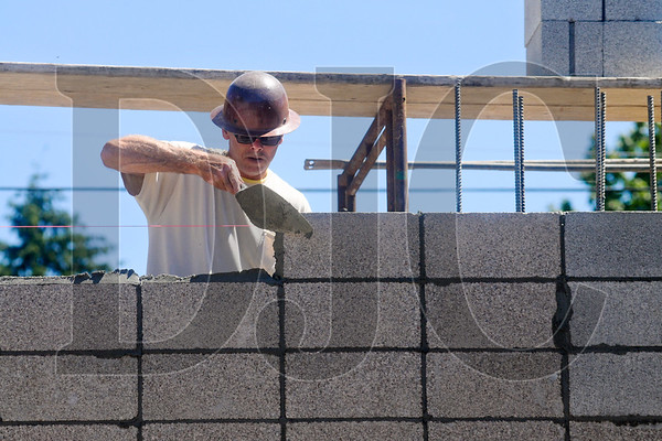 Don Keller, a mason with Creative Design Masonry, lays CMU on the Breathe Building.