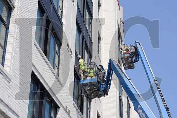 Crews with Northwest Masonry caulk windows and finish expansion joints on the exterior of the Parker Apartments.