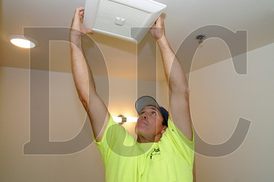 Charlie Hattaway, an HVAC installer with Jacobs Heating and Air Conditioning, installs a restroom fan.