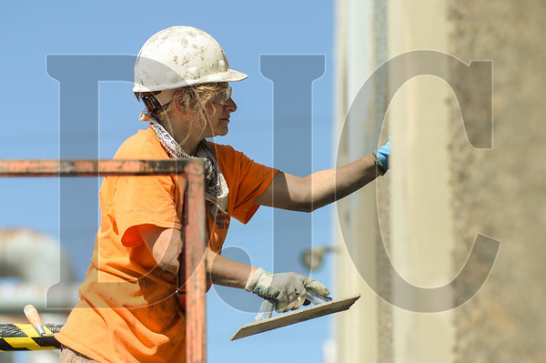 Rachel Eaton, a Journeyman Cement Mason with Cement Masons Local 555 and Whitaker Ellis Builders applies a patch to a concrete panel tilt wall as part of The Hopper project in Northwest Portland. (Josh Kulla/DJC)
