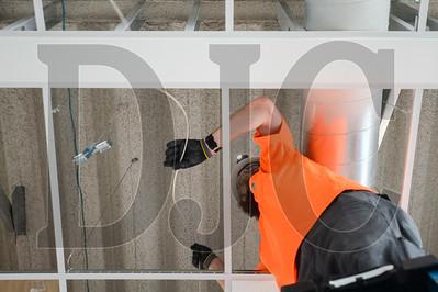 Journeyman Low Voltage Electrician Adrian Johnson of Applied Technical Systems installs sound masking equipment in Multnomah County's Gladys McCoy Health Department Headquarters building in Northwest Portland. (Josh Kulla/DJC)