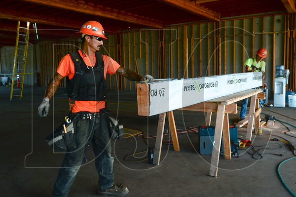 Apprentice Carpenter Miguel Cuevas and Journeyman Carpenter Ken Tomminger, both employed by R&H Construction, wrestle a glulam beam into place on the second floor of Building C on The Hopper campus in Northwest Portland. This building will be occupied by R&H Construction when complete. (Josh Kulla/DJC)