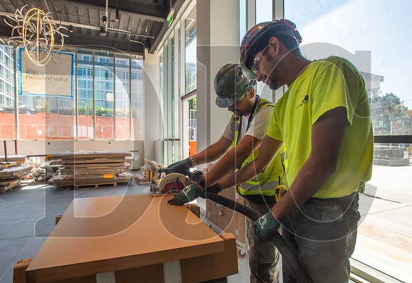 Francisco Franquez, foreground, and William Pelayo, both journeyman carpenters with Local 1503 and employees of Isec, Inc., assemble pieces of cabinetry for a ground-floor retail store. (Josh Kulla/DJC)