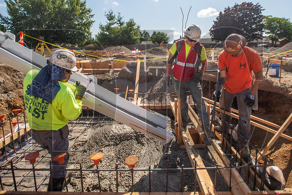 Journeyman carpenter Gerardo Carrillo, left, a member of Local 1503 and an employee of Whitaker Ellis, guides the concrete pour while fellow Whitaker Ellis and Local 1503 carpenter Rick Bird stirs the mix with a vibrator. (Josh Kulla/DJC)