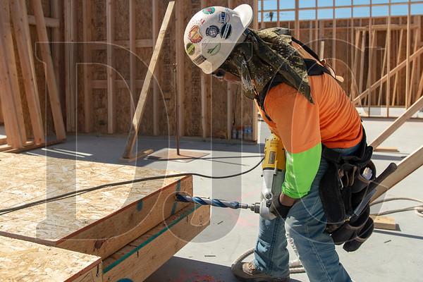 Wood Mechanix carpenter Lupe Arriago drills an anchor bolt hole in a wall panel. (Josh Kulla/DJC)