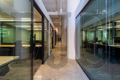 Glass doorways and wall panels are part of a wall system that allows for flexibility in office configurations. (Josh Kulla/DJC)