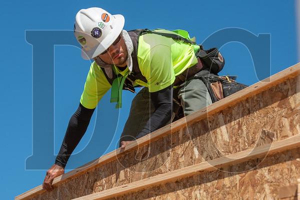 Wood Mechanix carpenter Jose Saucedo sets an I-joist in place. (Josh Kulla/DJC)