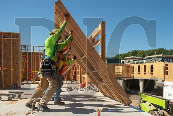 Wood Mechanix carpenters lift a wall panel into place. (Josh Kulla/DJC)
