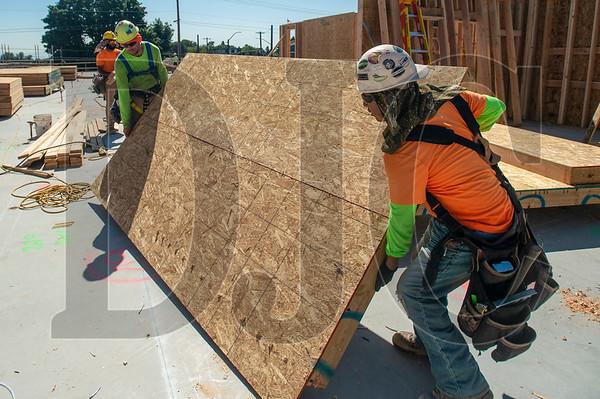 Wood Mechanix carpenters Robert Betschart, left, and Lupe Arriaga move a prefabridated wall panel. (Josh Kulla/DJC)