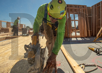 Robert Betschart, a carpenter with Wood Mechanix, trims the edge of a prefabricated wall panel at the Argyle Street Apartments in North Portland. (Josh Kulla/DJC)