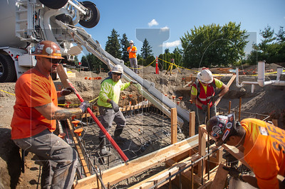 Employees of Whitaker Ellis Builders pour the foundation of an elevator shaft at Sifton Elementary School in Vancouver, Washington. (Josh Kulla/DJC)