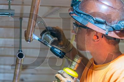 Apprentice plumber Sean Caires of Tapani Plumbing solders a hot water recirculation line. (Josh Kulla/DJC)