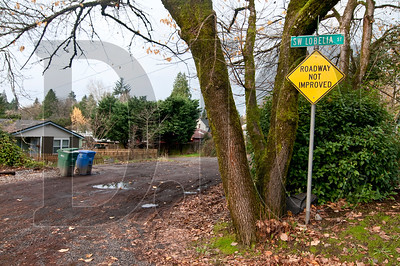 A sign warns of unpaved road at the intersection of Southwest Lobelia Street and 8th Avenue in Portland. Because the city has never paid for paving residential streets, approximately 60 miles of dirt and gravel roads exist in Portland.