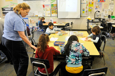 Pamela Russell, left, helps students with an assignment in her first- and second-grade classroom at Rosa Parks Elementary. The DOWA Architects-designed school features classroom pods with windows that look onto common areas, inspiring collaboration between students and teachers.
