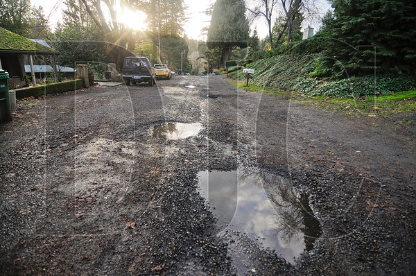 Puddles of water dot the street on Southwest Plum Avenue in Portland, part of the approximately 60 miles of unpaved roads in the city. A new city initiative will make it less expensive for residents on unpaved streets to pay for street paving and sidewalks.