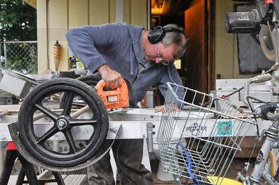 Chris Sanderson cuts a piece of wood on a workbench that also serves as his bicycle trailer while working on a home in North Portland. Sanderson, the owner of Builder by Bike, uses a bicycle to transport himself, tools, and materials to job sites.