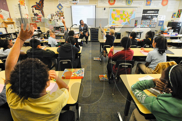 Stephanie Windham, top center, gives a lesson in her fifth-grade class at Rosa Parks Elementary. The school's design, which features classrooms built around common areas, is the new standard for Portland Public Schools and will become more commonplace as older campuses are updated.