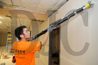 Apprentice finisher Travis Robello uses a bazooka to tape a seam in a classroom space.