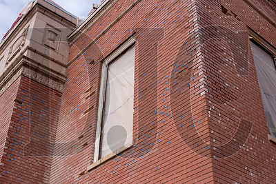 Bricks on the 1923-era gymnasium building that are in need of replacement have been marked with colored tape.