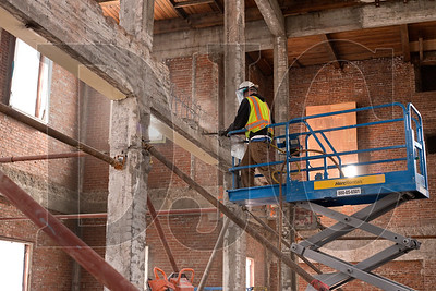 An employee ofNorthStar demolishes concrete in the original gymnasium building.