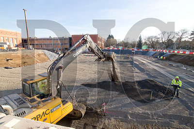 Crews are pouring the rock pad for the foundation of a new two-story gymnasium.