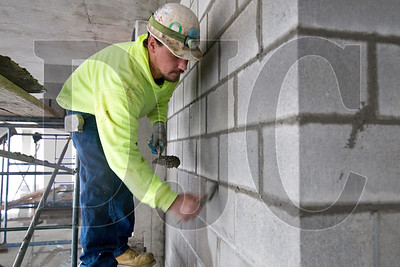 Portland Masonry employee Darrel Urban blocks in a third-floor elevator shaft.