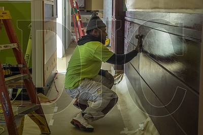 Journeyman painter Arrick Sneed, an employee of Rogers Painting, applies wood finish to paneling inside the new Mothers' Bistro restaurant.