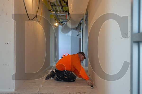 Journeyman laborer Luis Carrillo, a member of Local 737 and an employee of Ultra Quiet Floors, installs flooring.