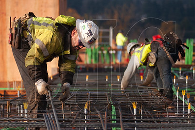 Journeyman ironworker Arturo Bojorquez, left, and apprentice Shawn Strock, members of Ironworkers Local 29 and employees of Bar M Steel, lay rebar on the first deck of the Axletree mixed-use project in Milwaukie. (Josh Kulla/DJC)