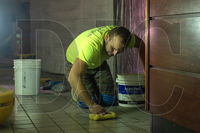 Nick Rudeichuk, a tile installer with Provenzano's Tile Installation, cleans freshly laid tile in a hallway at the new Mother's Bistro location in downtown Portland. (Josh Kulla/DJC)