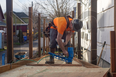 Bremik Construction Superintendent Josh Coleman nails down sheets of plywood for a wheelchair ramp being built at a North Portland residence by Bremik employees as part of a holiday community outreach program. (Josh Kulla/DJC)