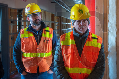 Walsh Construction Project Engineer Brian Ames, left, and former Central City Concern CEO Ed Blackburn, the building's namesake, tour project.