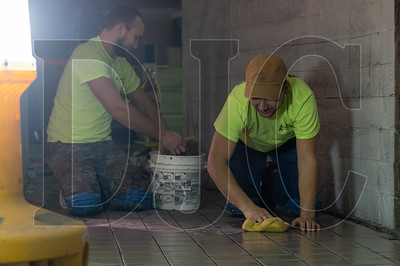 Brothers Dima Rudeichuk, right, and Nick Rudeichuk, both tile installers and employees of Provenzano's Tile Installation, clean a freshly laid set of tiles on the job site of the new Mother's Bistro restaurant. (Josh Kulla/DJC)