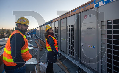 Walsh Construction Project Engineer Brian Ames, left, and Marketing Director Maren Sinclair inspect rooftop HVAC condensor units at the Blackburn Center.