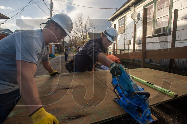 Bremik Construction employees Matt Dalla Corte, Director of Project Development, and Jeremy Symolon, a Superintendent, measure and cut sheets of plywood for a wheelchair ramp as part of the company's holiday outreach partnership with Reach CDC. (Josh Kulla/DJC)
