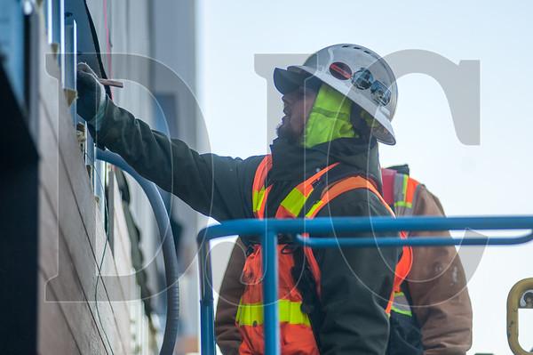 Journeyman sheet metal technician Sam Stafford installs cladding at the Blackburn Center.