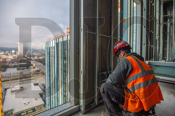 Austin Craft, an apprentice electrician with IBEW Local 48 and Cherry City Electric, roughs in a wall receptacle on the 16th floor of 5 MLK. (Josh Kulla/DJC)