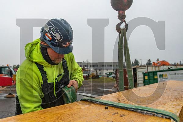 Journeyman carpenter Jarrett Dean of LMC Construction prepares the rigging for a glulam beam. (Josh Kulla/DJC)