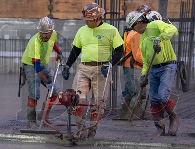 Mario Ornelas, second from left, operates a gas-powered concrete screed as a crew of cement masons finish a section of foundation slab. (Josh Kulla/DJC)