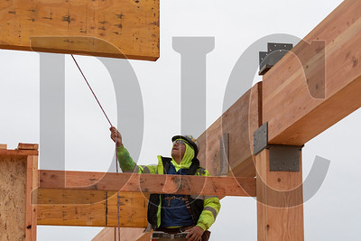 Journeyman carpenter Marcos Rosas of Timberland Inc. guides a glulam beam into place at the Rockwood Rising project site in Gresham. (Josh Kulla/DJC)
