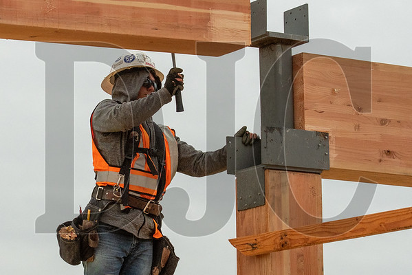 Jesus Antonio guides a glulam beam into place on the third floor. (Josh Kulla/DJC)